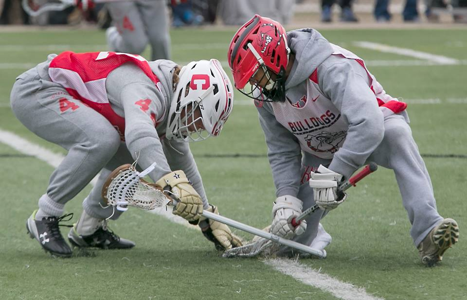 Senior KJ Howard wins a face-off in the cold against Colleyville Varsity.