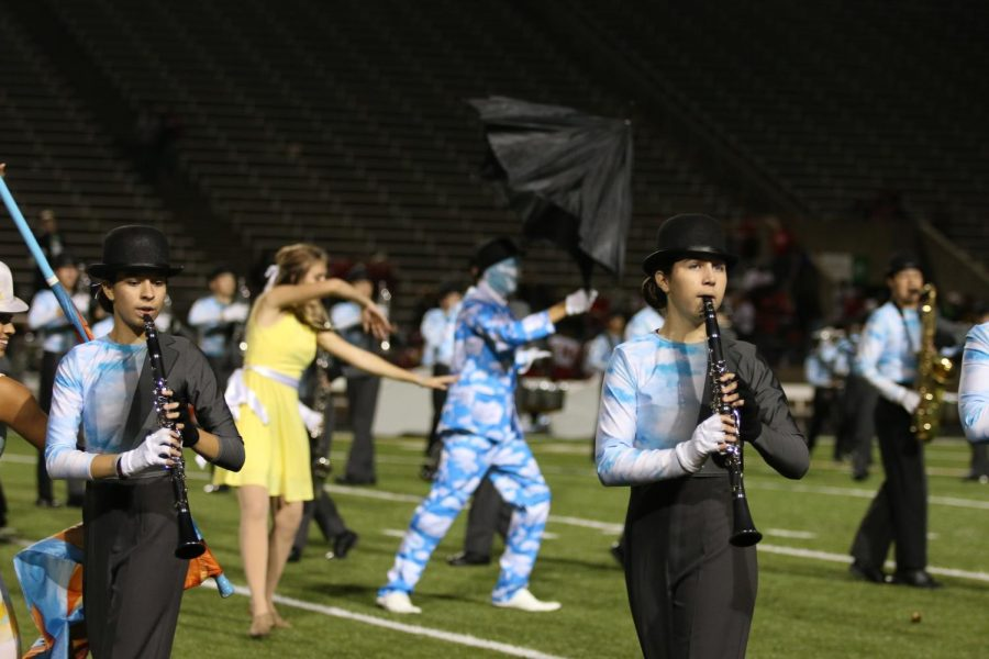 Sophomores+Lauren+Thomason+and+Brooke+Fertig+perform+one+of+their+routines+during+halftime%2C+with+marching+band+and+color+guard.
