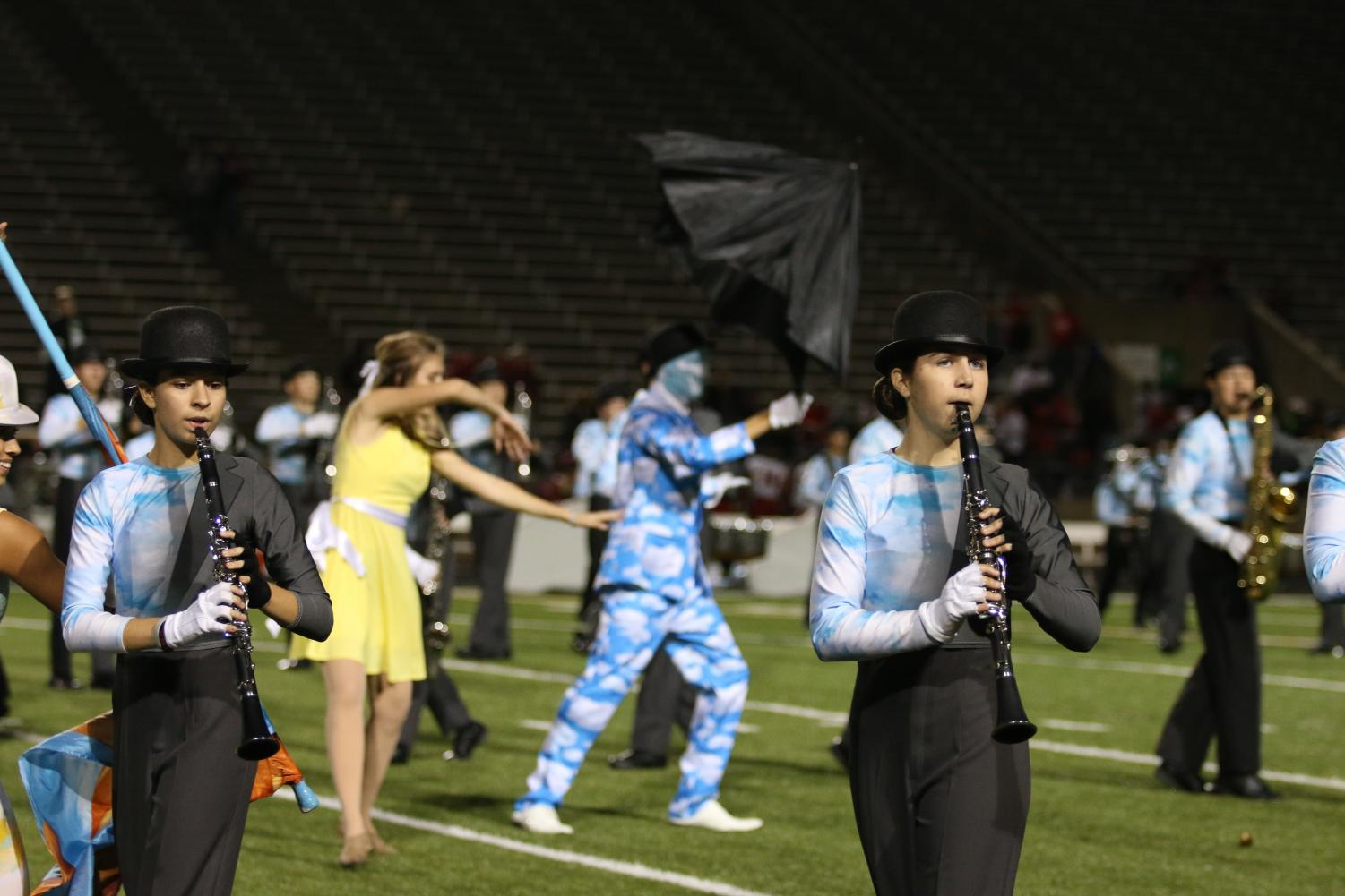 Sophomores Lauren Thomason and Brooke Fertig perform one of their routines during halftime, with marching band and color guard.