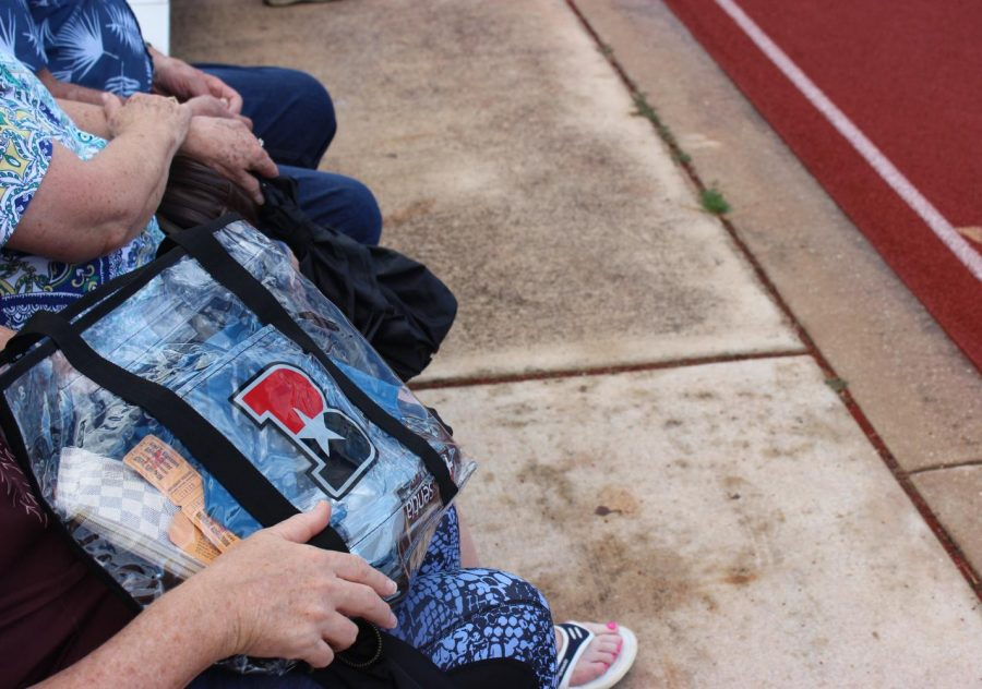 Family of Bowie athlete cheer from the sidelines with their clear bag, courtesy of the new policy.