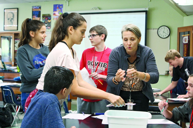 HANDS-ON DEMONSTRATION: Biology teacher Stacie Feen shows freshmen Sophia Moawad and Matthew Elam a demonstration of their lab. Feen teaches Pre-AP Biology.