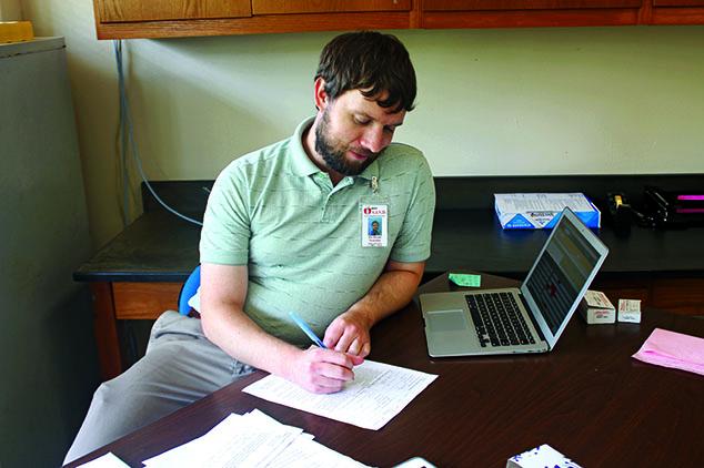 EYES ON THE PAPER: Teacher Eric Krauss grades a students assignment.  Krauss made the transition from Kaktovik, Alaska to Austin to teach.