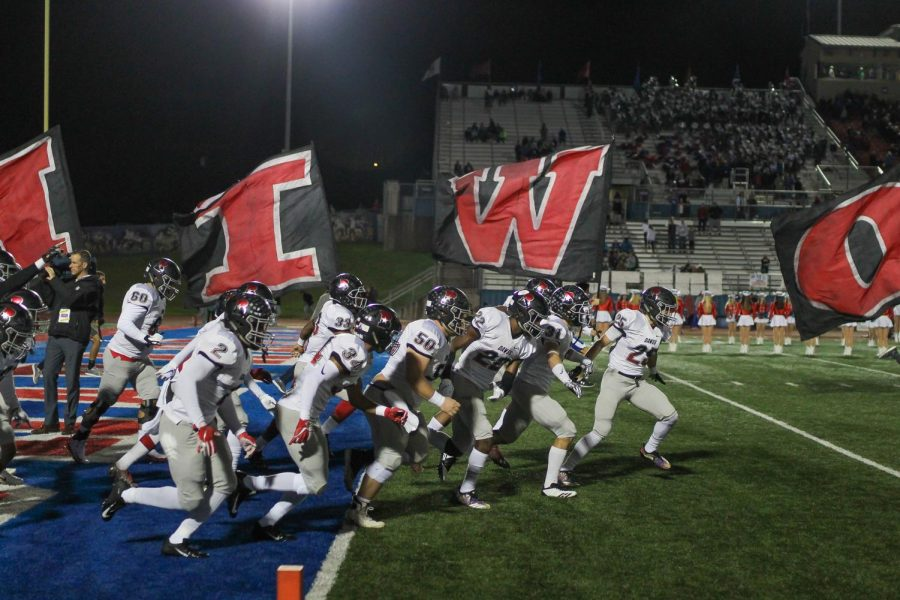 Charging+out%3A+The+Bowie+Varsity+football+team+storms+out+of+the+big+bulldog+at+the+start+of+the+game.+The+Bowie+vs.+Westlake+game+happens+annually%2C+and+students+from+both+schools+are+eager+to+attend.+%E2%80%9CThis+game+is+always+fun+because+Westlake+is+a+challenging+team+to+beat%2C%E2%80%9D+senior+varsity+player+Kendrick+Neptune+said.+%E2%80%9CEven+though+we+lost%2C+I%E2%80%99m+proud+our+team+played+hard.%E2%80%9D