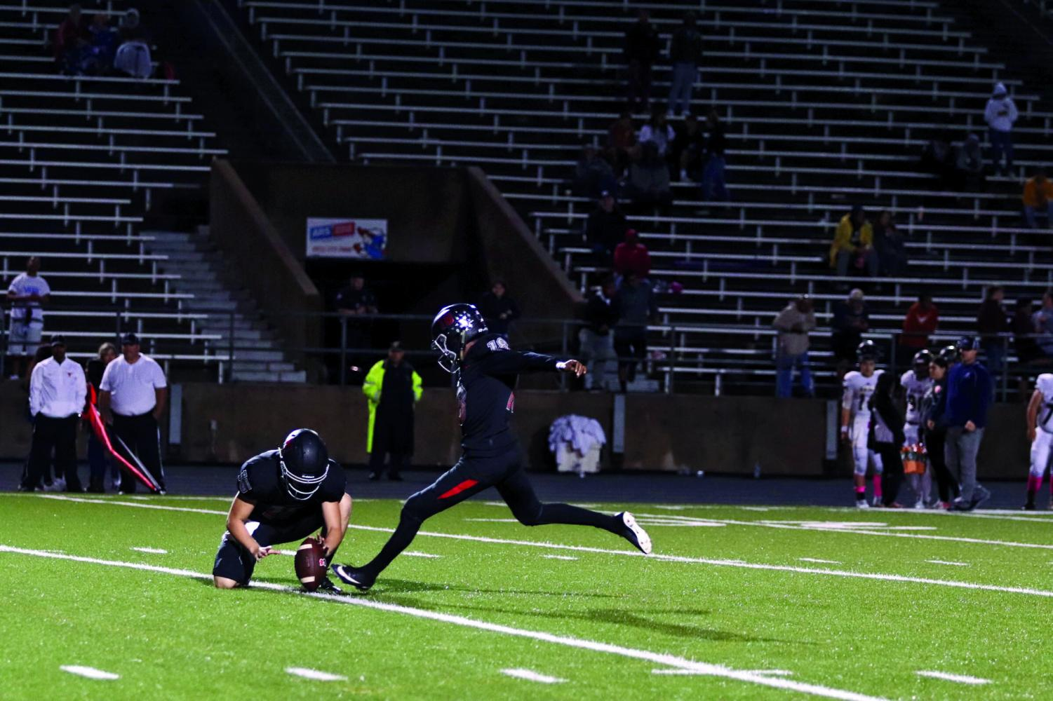 HERE'S THE KICKER: Sophomore Josh McCormick kicks a field goal as senior Aiden Ellisor holds the ball in place. McCormick, Ellisor, and the Bowie Bulldogs won the game against  the Akins Eagles 49-29 with McCormick drilling seven extra points to stay perfect this season.