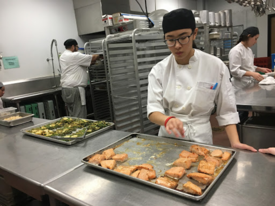 Senior, Asia Vo prepares her very own garlic spice honey glazed salmon at her Bee's Knees luncheon.