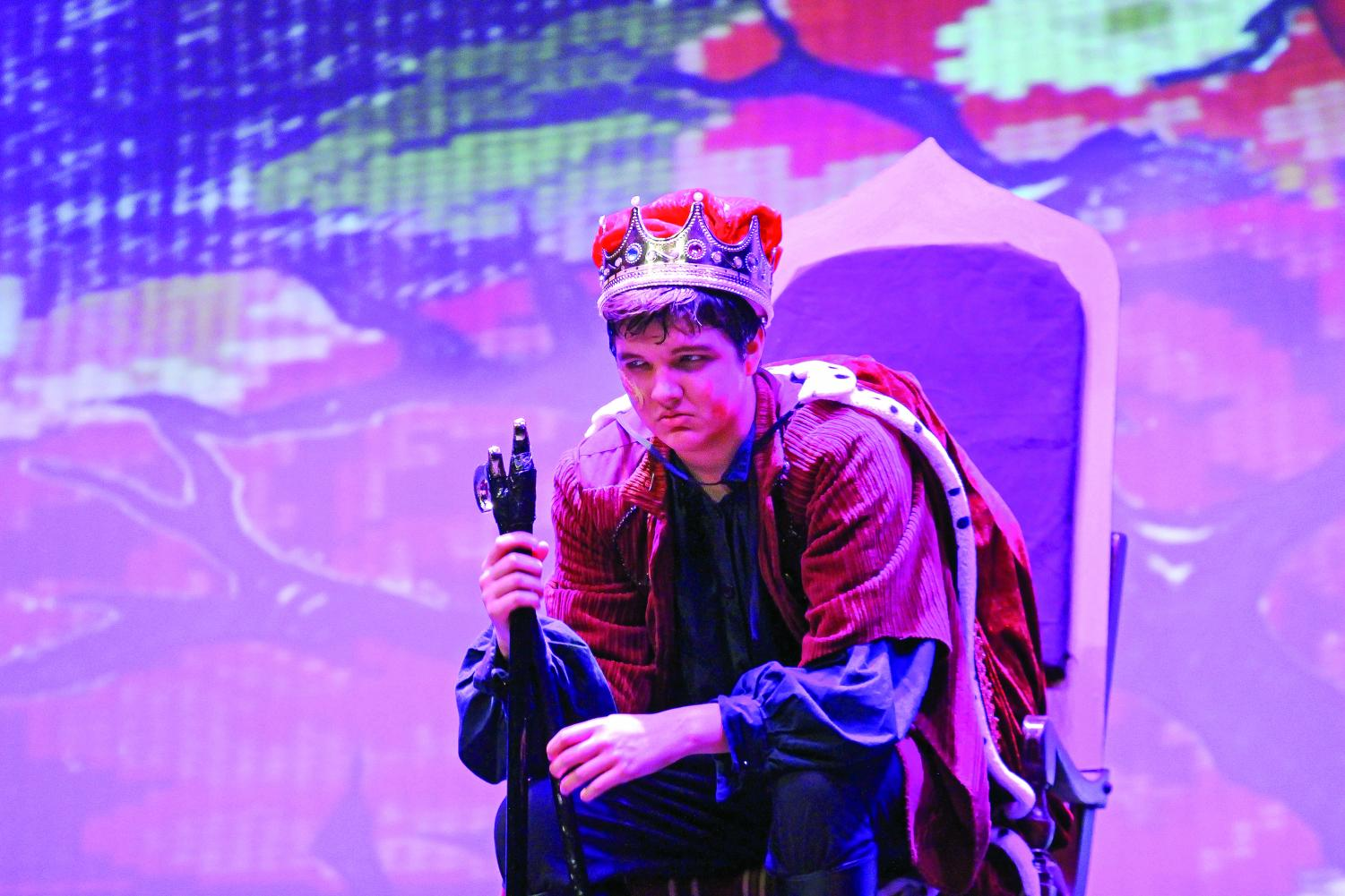 Gloucester glares at his subjects: Senior Ben Harmon, acting as Gloucester, sits in his throne after he has become king. Harmon sets the scene of his rise to power and newfound authority with an angry glance at his fellow castmates who are approaching him. Harmon continually radiates an aggressive attitude to get into character.