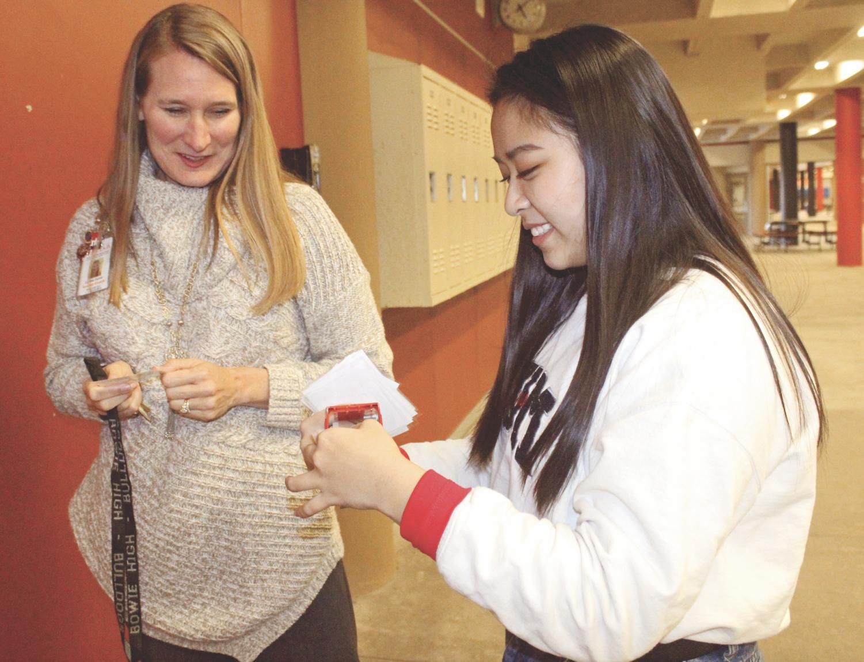 LENDING SOME LOVE: Senior Lin Tran helps Cindi Carroll hang badges on teachers' doors after school. Tran helps out Carroll of ten as part of Helping Hands.