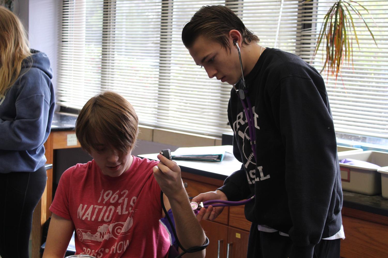 Feeling the Pressure: Junior Walker Smith takes junior Liam Kornacki blood pressure during a lab in AP Biology.