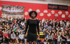 Seun Odufuye walks down the center of the gym down to her seat alongside other members of the JBHS multicultural awareness club. The MCAC worked all year to promote unity.