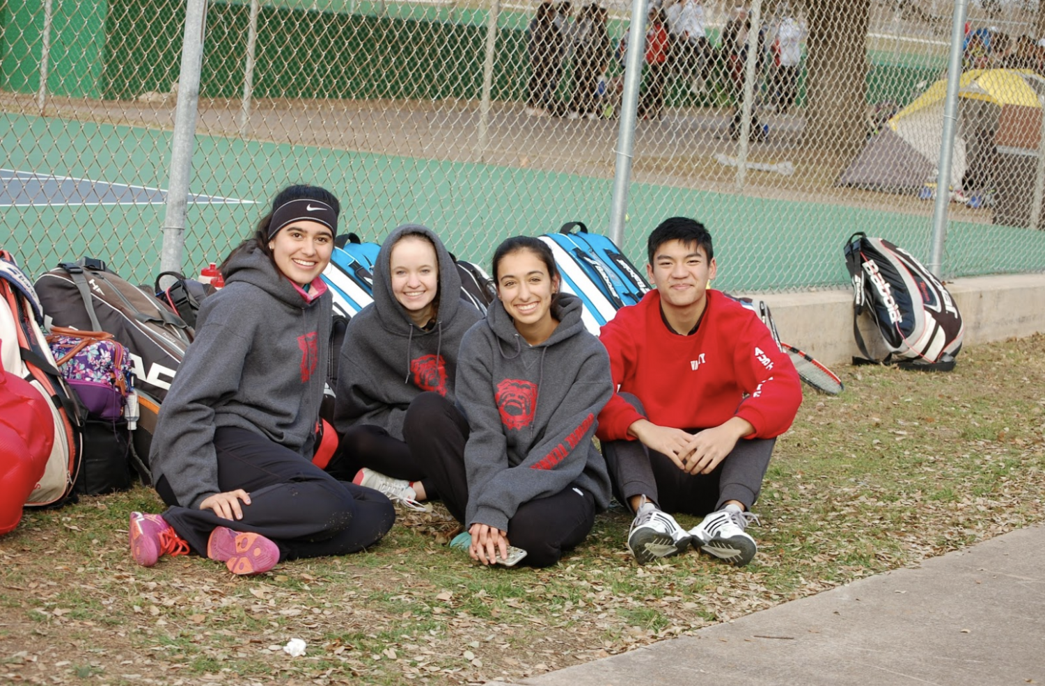 Waiting in anticipation: Emily Leeke, Kayleigh Shumaker, Sydney Johnson, and Stephen Do huddle together in the cold while waiting for their next match at UT Whitaker courts.