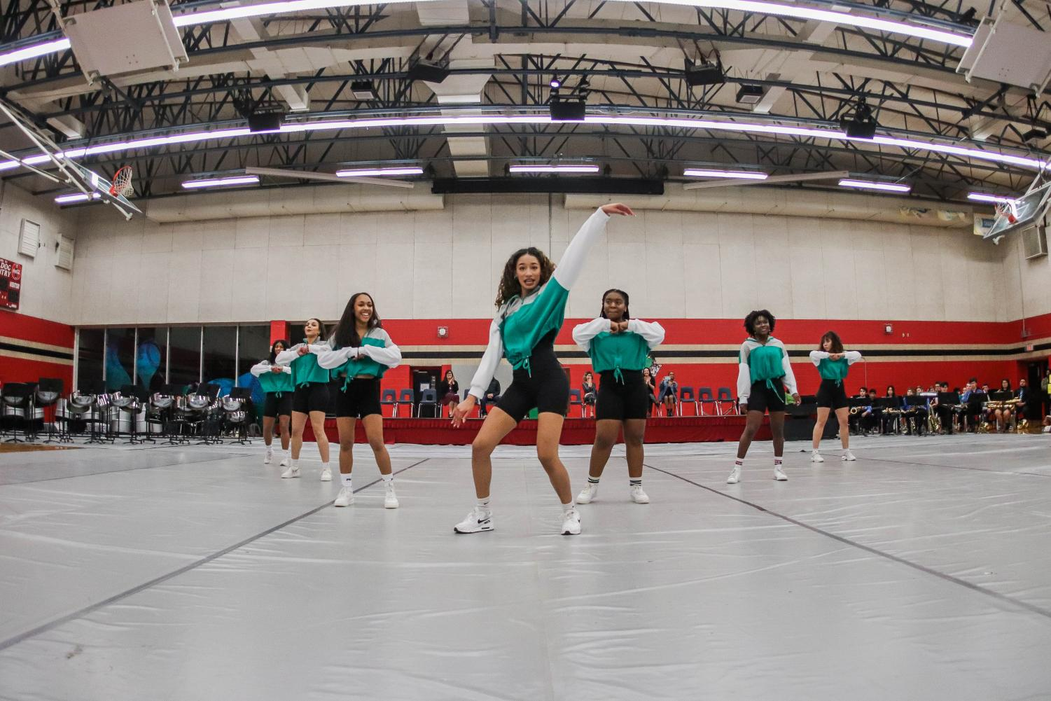 (Left to right) Kiara Gonzales, Kaeleigh Chambers, Lisa Wilkerson, Nyah Bernucho, Camron Sneed, Seun Odufuye, and Gia Spencer dance as part of the Multi Awareness club for hundreds of students  in the JBHS Black History Month assembly in front of the main podium. Both gyms were open for the event, with the performance covering the small gym's floor while students are seated, elevated in the larger gym.