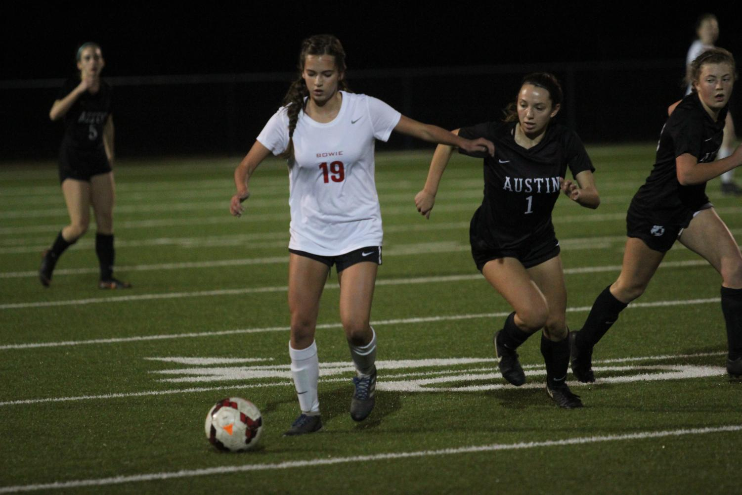 GETTING A KICK OUT OF IT: Senior Hannah Erb outpaces her opponent. Erb is one of the two team captains of the varsity girls soccer team.