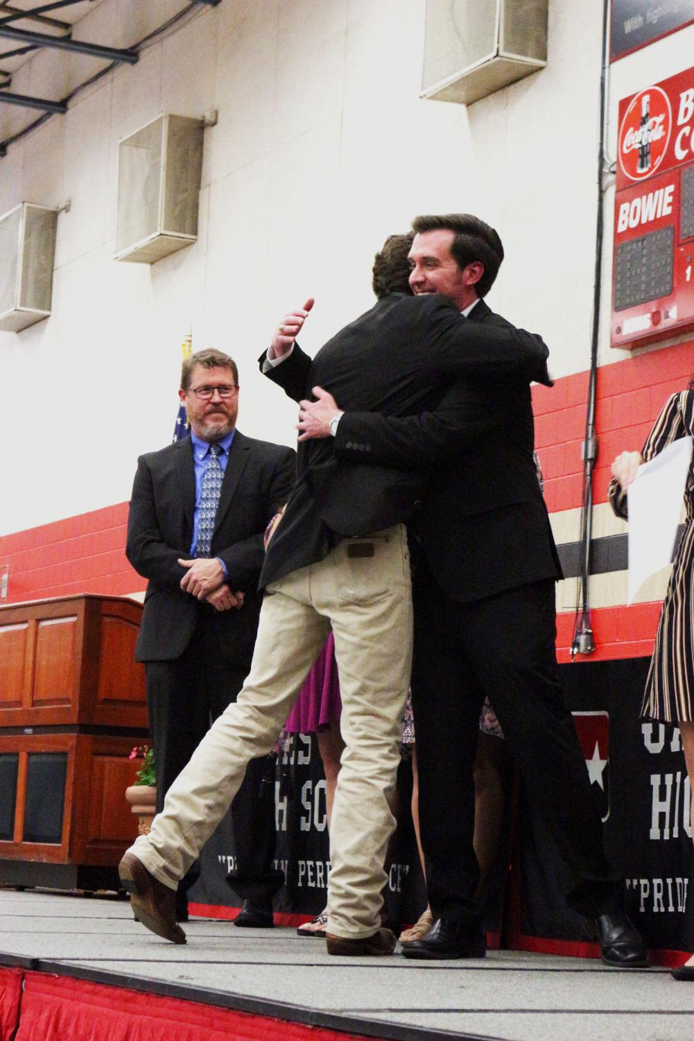 FINAL GOODBYES: Adam Werchen embraces social studies teacher Alejandro Garcia as he accepts an award at senior honor night. Principal Mark Robinson observes the excitement and positivity of the event to the left.