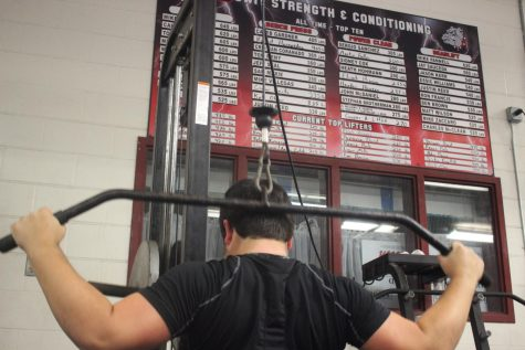 POWER AND DETERMINATION: Junior power-lifter Evan Janacek performs lat pull-downs. Janacek is currently ranked as one of the top lifters at Bowie.