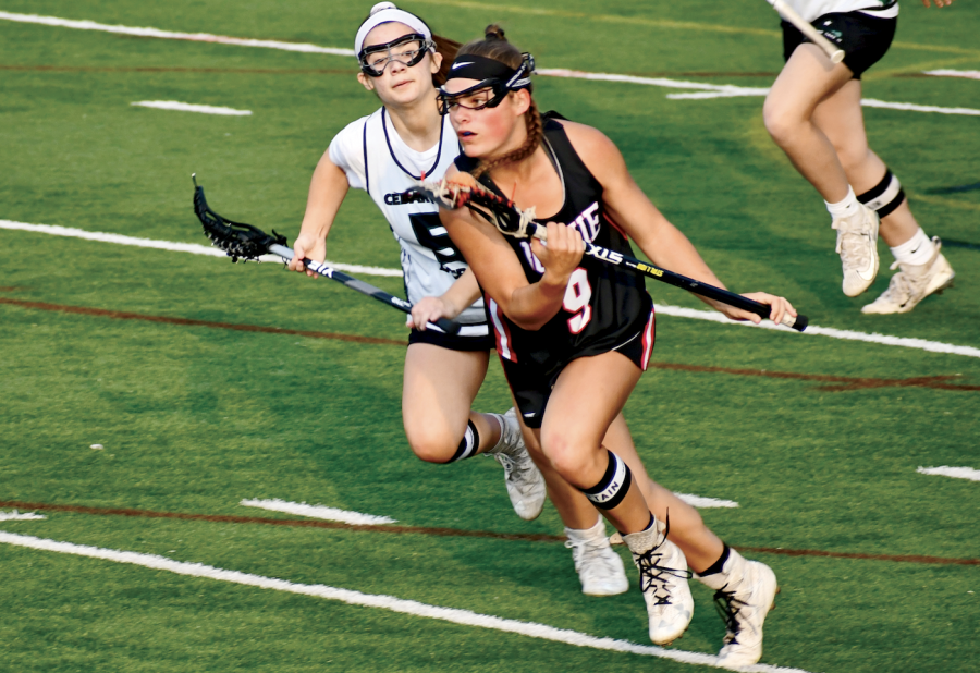 ON+THE+MOVE%3A+Junior+Sydney+Heim+sprints+down+midfield+towards+the+goal.+Heim+was+awarded+with+All-American+and+All-State+honors+this+season.+