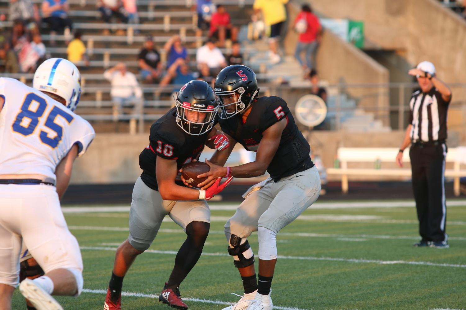 HAND OFF: Quarterback Trinidad Sanders, senior, hands the ball off to senior running back Justin Poole.