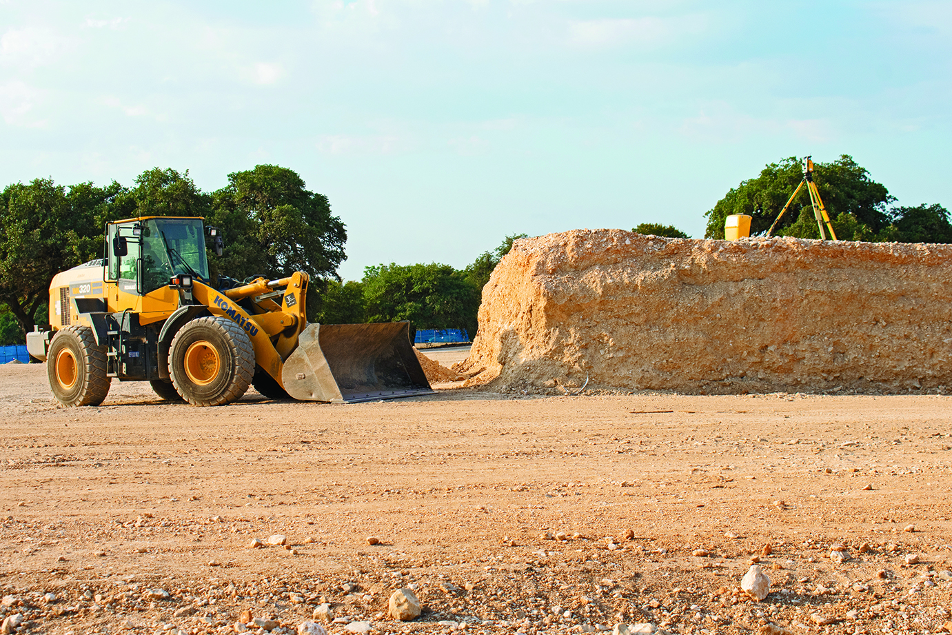 DOWN IN THE DIRT: A front loader is parked by the dirt mound which will be a part of the mound in the parking garage. The laser mounted on the tripod on top of the mound is used to establish grade and elevation of the parking garage.