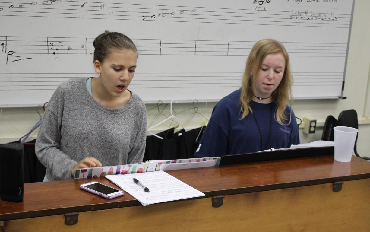 REHEARSING: Sophomores Kaelie Douglass and Carson Haley sit at the piano and rehearse their songs for the choir region competition.