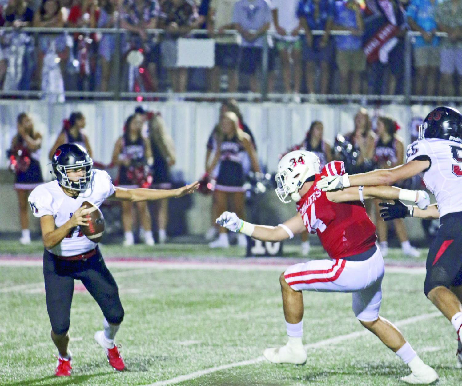 STAR PLAYER: Sophomore quarterback Diego Tello searches for a target as his opponent charges at him. Tello will be one of the varsity starting quarterbacks for the rest of this season.