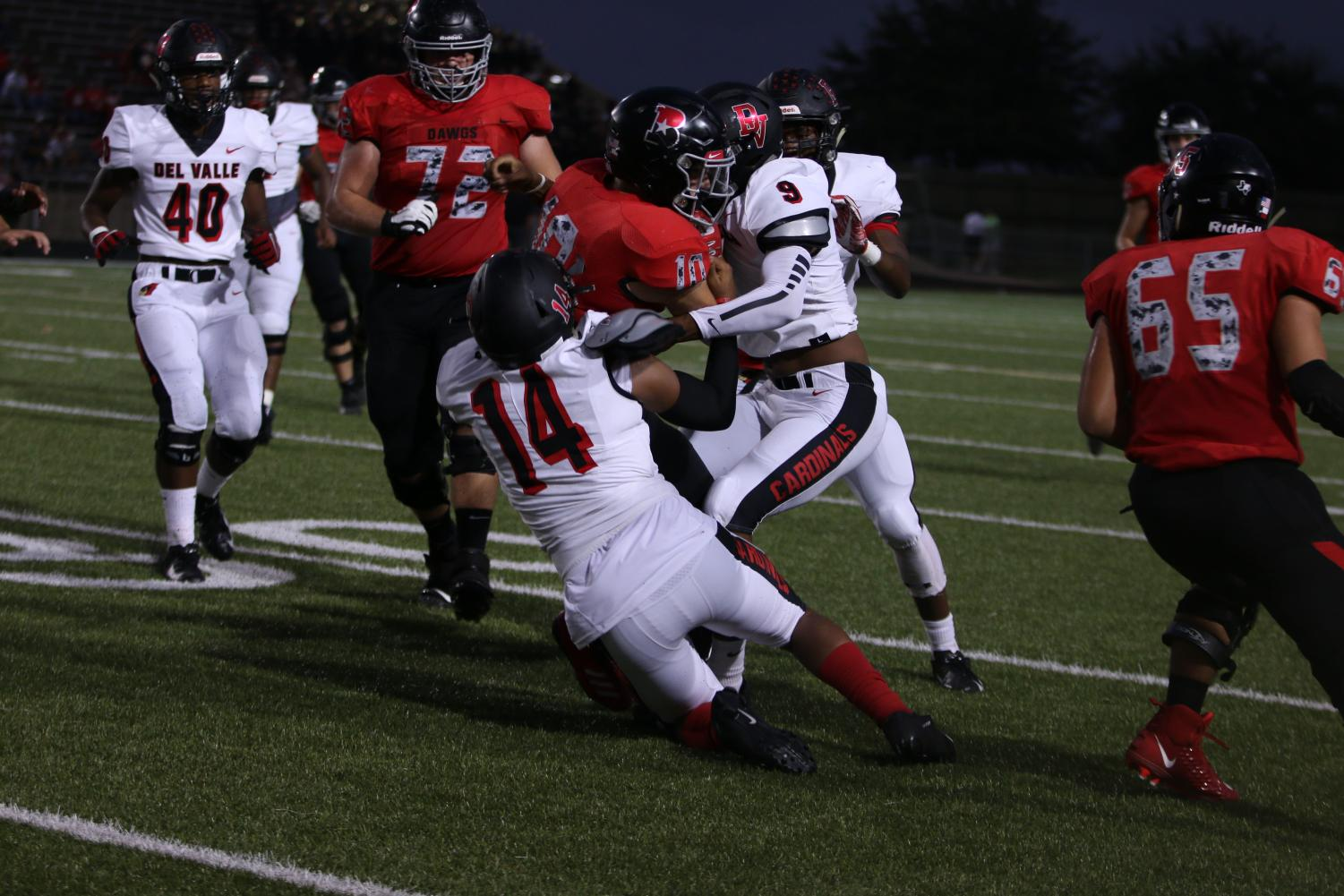 The varsity team tries to get the ball through Del Valle's defense. The play ended with a tackle, and the ball falling.