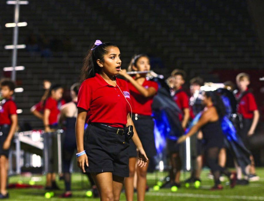 LOUD AND TUNEFUL: In the half-time performance, senior Hannah Cherukuri sings in The Apotheosis. Cherukuri had to focus on her volume to make sure everyone in the audience could hear her vocals while the band was playing right behind her.