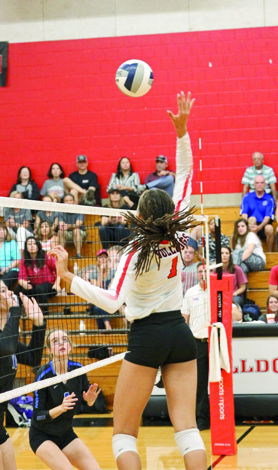 BUMP, SET, KILL: Junior middle blocker Maya Johnson hits the ball back on to Ann Richards' side of the court. Because of her performance, she has received interest from several colleges.