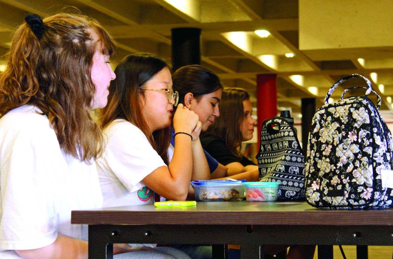TIME FOR LUNCH: Sophomores Adelaide Sibley, Erica Lee, and Andrea Hascribein (from left to right) enjoy lunch at one of the many side-table options across camp. In accordance with the new policy, students cannot sit in A,B,F, or E hall during lunch, however, C and D hall are available for use.