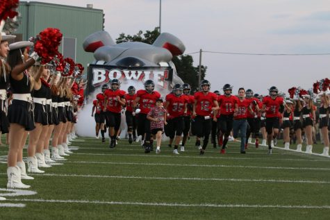 HARD AT WORK: The varsity football tam runs on to the field to begin a game. Photo by Peter Dang