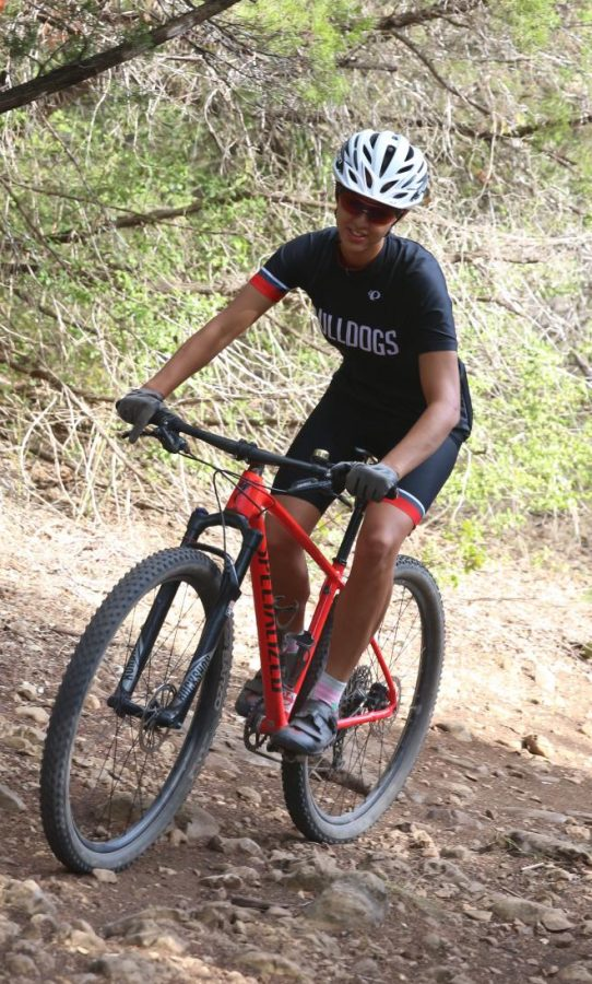 ROCKY ROAD: Ann Richards senior Emily Doucette navigates her way through the rough trail on her bike. Doucette wears special shoes, padded shorts, a helmet, and glasses to help keep her safe while she rides.