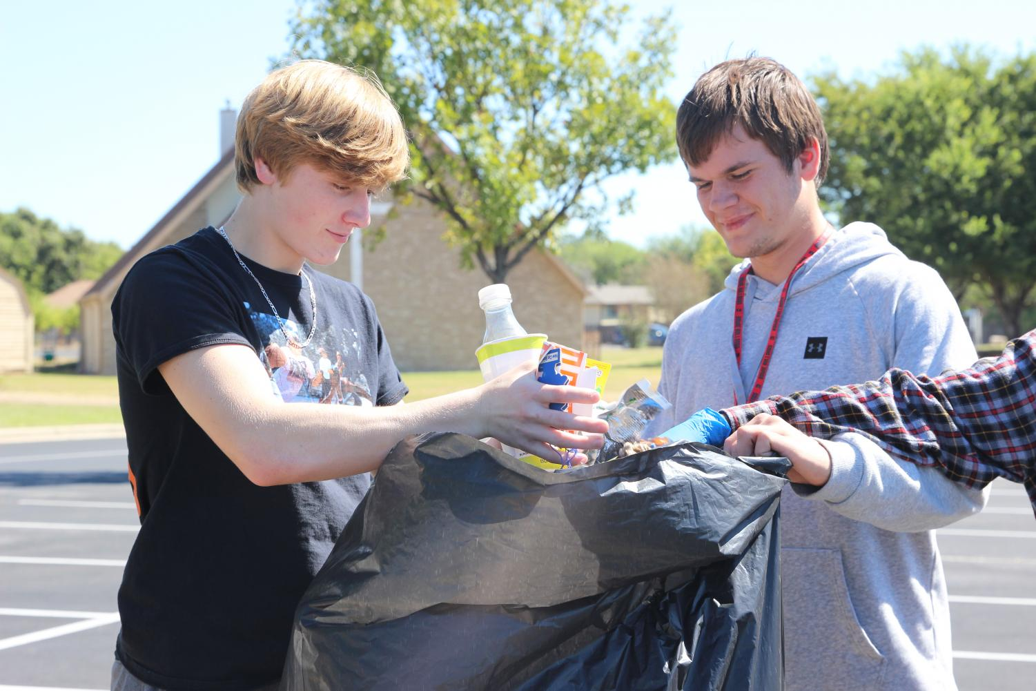 CLEANING UP FOR GOOD: Tye Frnka and Evan Mallett discard litter from the West Oak Woods Baptist Church parking lot with fellow club members. Various clubs have been cleaning up the parking lot for the past month in order to maintain parking lot privileges.