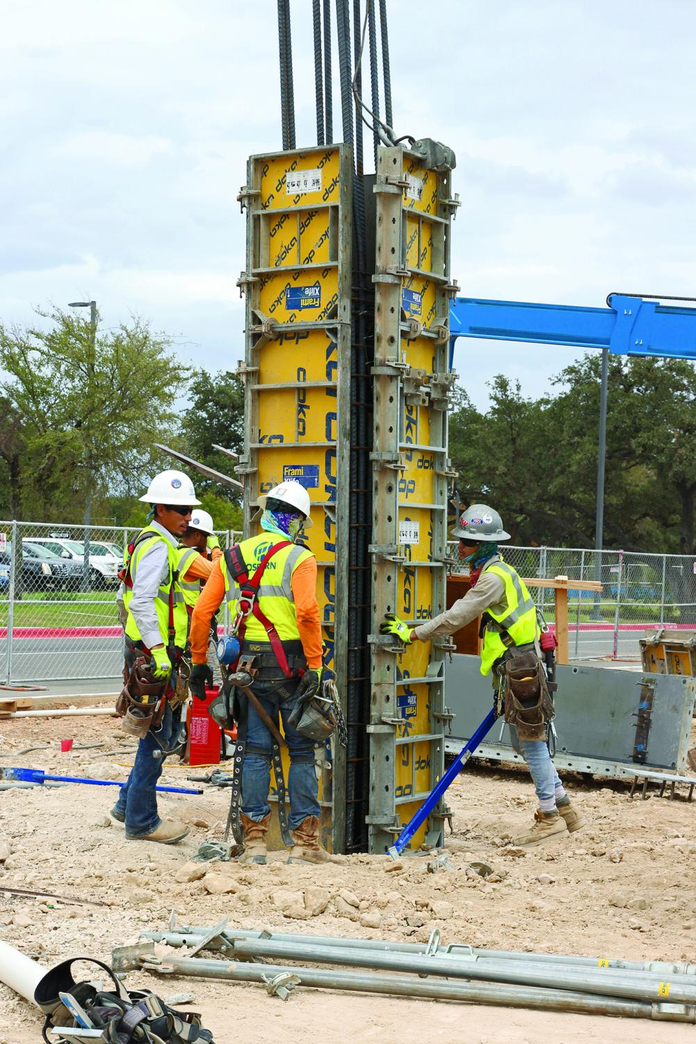 TOTAL TEAMWORK: Construction workers set up a concrete form for a column. Columns are poured on top of underground piers.