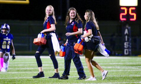 "HANDING OUT WATERS: Seniors Cara Spradling, Sarah Clements, and Caitlyn Sanchez walk off the field from delivering water to the players.  Spradling has been a trainer for two years and has seen lots of injuries. ""This one kid on the freshman team had bursitis and I got to tape it and when we got back to the trainers got to help pop and drain it,"" Spradling said. ""I really enjoyed it because I got hands on experience with injuries."""