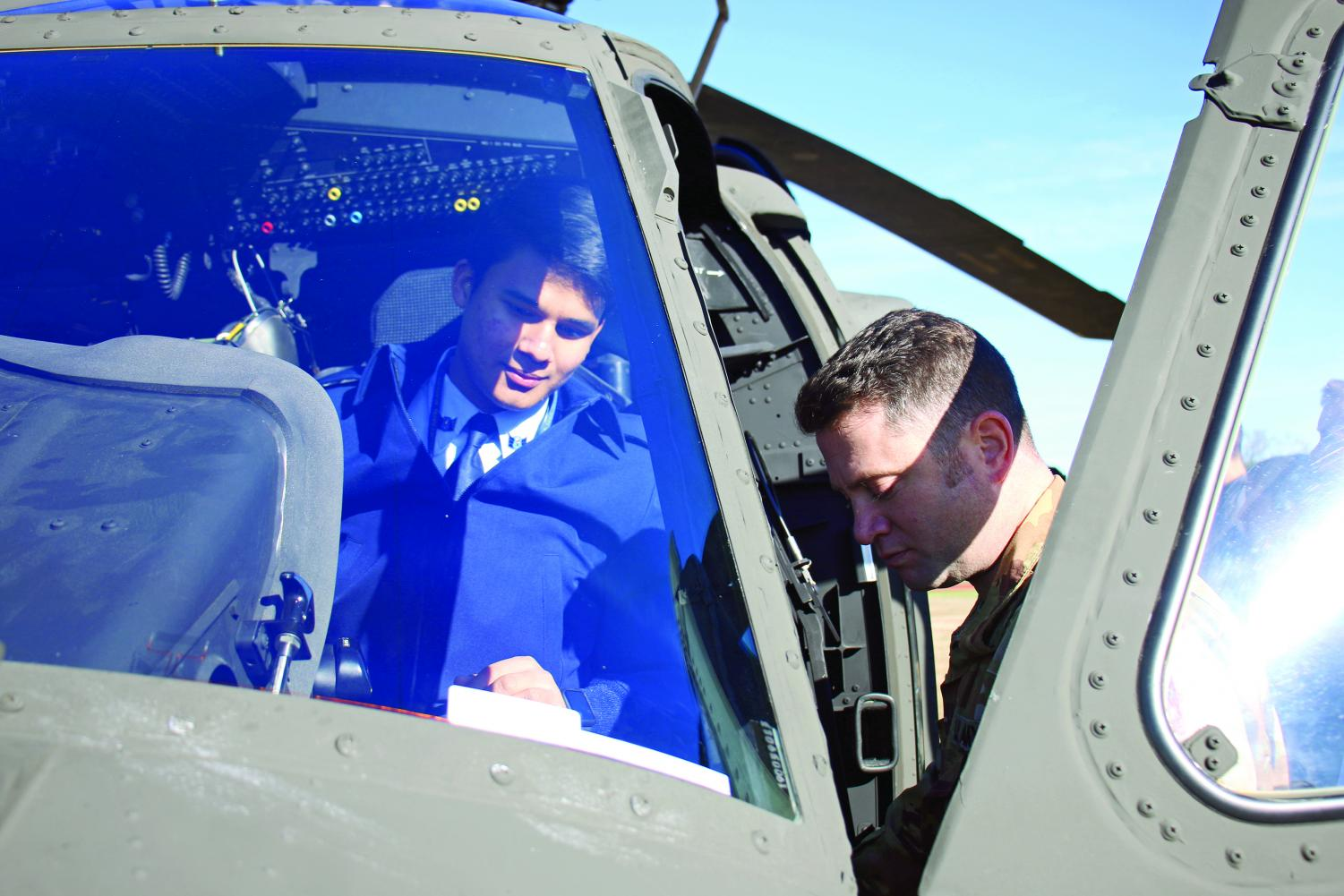 HANDS ON: Chief Warrant Officer Billy Black shows senior Walter Esparza the helicopter flight controls. Black was a cadet in JROTC when he attended Bowie.