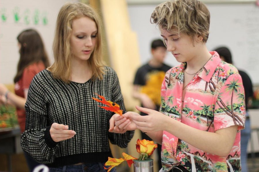 """DECIDING WHERE TO PLACE THE LEAF: Sophomores Ava York and Colette Waid discuss how they want their floral design to look. Both decided to join the class because they wanted to work with flowers. """"I'd really like to work in a floral nursery or floral shop in the future,"""" Waid said. """"So this was the best option for that."""""""