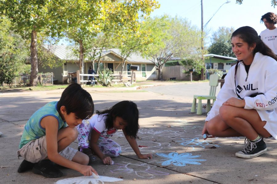 Sophomore Cristina Canepa laughs alongside two children as they paint the sidewalk with chalk. When a student under 18 volunteers at the family shelter, they must have an adult present. *Identities of the non-high school students have been withheld for privacy reasons.