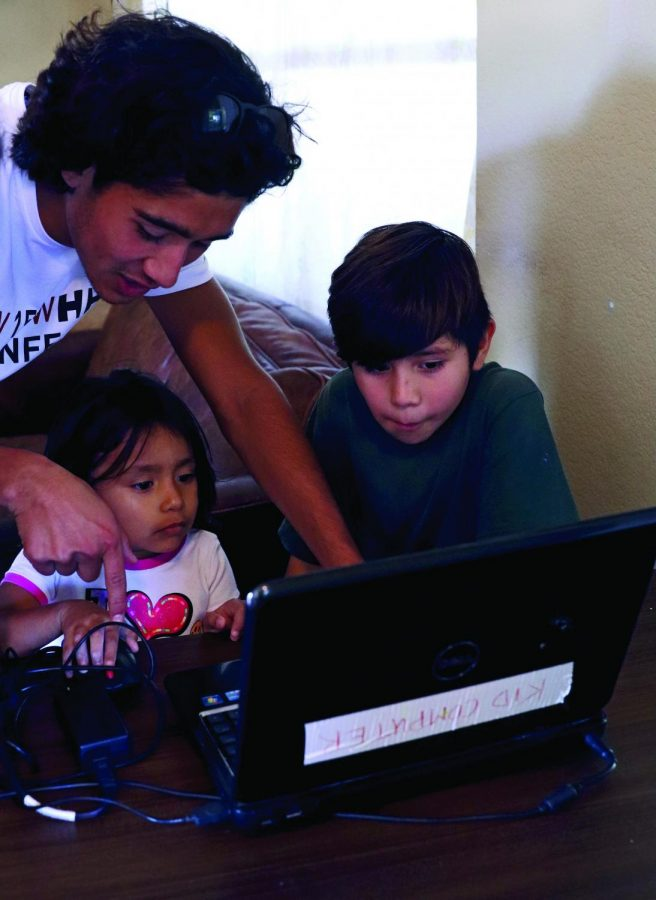 SERVICE WITH A SMILE: Senior Carlos Canepa leads two kids in a computer lesson. The shelter uses volunteers to provide academic tutoring services for their residents. *Identities of the non-high school students have been withheld for privacy reasons.