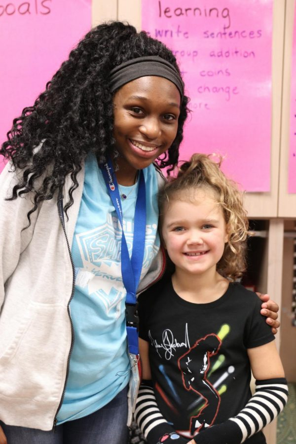FROM TEACHER AID TO HERO: Senior Cyn'torreya Smith embraces her second grade student Moxie Maxwell. On Dec. 4, Smith performed the Heimlich maneuver on Moxie when she began choking during lunch.