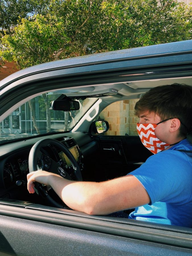 Junior Liam Spencer drives to a local business to receive his purchase via curbside delivery. The new curbside retail is the first part of Governor Abbott's new plan too slowly begin the reopening process in Texas. A full plan for reopening is expected to be released at a press conference; however, the exact date of said conference has not been announced.