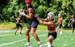 Junior varsity wide receiver Thanio Bright (left) receives a pass. Follow @thaniobfit on Instagram to stay updated on his athletic journey.