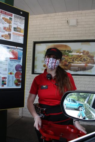 Junior Brooke Forsyth poses for a photo while working a shift at Sonic. Under Texas Governor Greg Abbott and Austin Mayor Steve Adler's orders, essential businesses such as restaurants like Sonic will remain open during quarantine but must follow social distancing policies.