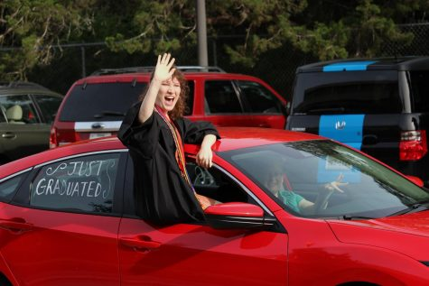 Senior Elizabeth Cluchey beams as she waves to her beloved teachers. Cluchey said that upon reflection of her high school career, it would be the family she had in the Starlight Theatre Company that she will miss the most.