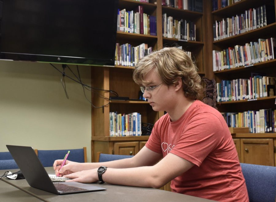 Junior Chris Thompson participates in remote learning from his father's office after Google Fiber's service was disrupted at his home. On Sept. 11, Google Fiber had several outages across the nation, causing students to seek alternative methods of internet connection to complete online class work.