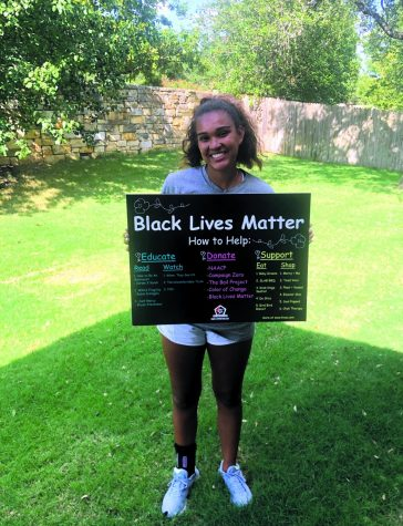 SIGN IN HAND: Smiling with her sign, senior Vivian Howard shows off her creative work. Howard created the sign last summer to help educate on the Black Lives Matter movement.