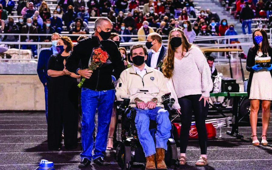 MASKS ON: Senior Evan Mallett poses for a photo with his family before heading onto the field to receive the nomination for Homecoming King. Along with being named Homecoming King, Mallett was chosen by his team as a Varsity Captain for the 2020 football season.