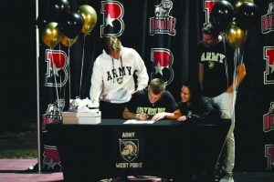 OFF TO THE BIG LEAGUES: Coleton Benson officially signs to Army West Point for basketball as his family gathers around to watch. Benson has been playing basketball for the majority of his life and is excited to be able to continue his career at the college level.