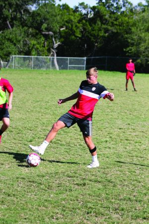 EYES ON THE BALL: Soccer team captain Keegan Hardy controls the ball in the team's scrimmage with the tracer strapped onto his left leg. The team's season doesn't start until mid-December.  PHOTO BY Michael Reeves