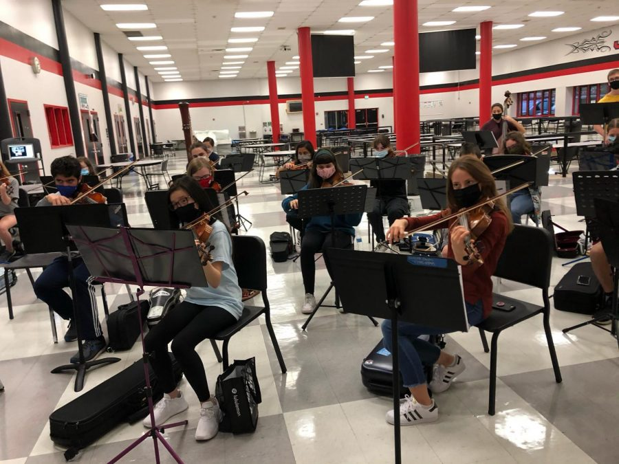 PRACTICE+MAKES+PERFECT%3A+Students+in+the+top+orchestra+get+together+to+practice+at+school.+Students+practice+Tuesdays+after+school+in-person%2C+however+on+other+days+they+practice+virtually.+
