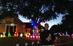 """IN FRONT OF HIS DISPLAY:  Baseball coach Sam Degelia poses with his light display in front of his house. Degelia spent six days getting out, setting up all the decorations, and syncing them up with music. """"My favorite part of the decorations are when we put music to the lights and watch them move to whatever song is playing,"""" Degelia said. """"The LED lights are really colorful and bright. So these stand out from some of the other lights."""""""