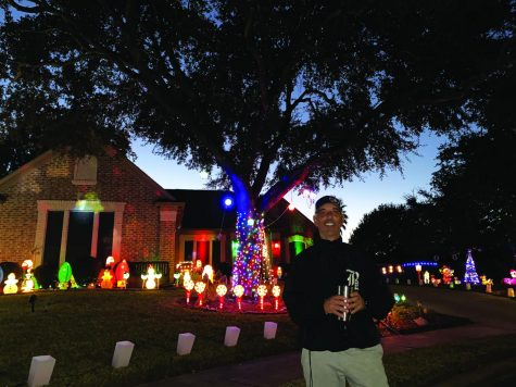 "IN FRONT OF HIS DISPLAY:  Baseball coach Sam Degelia poses with his light display in front of his house. Degelia spent six days getting out, setting up all the decorations, and syncing them up with music. ""My favorite part of the decorations are when we put music to the lights and watch them move to whatever song is playing,"" Degelia said. ""The LED lights are really colorful and bright. So these stand out from some of the other lights."""