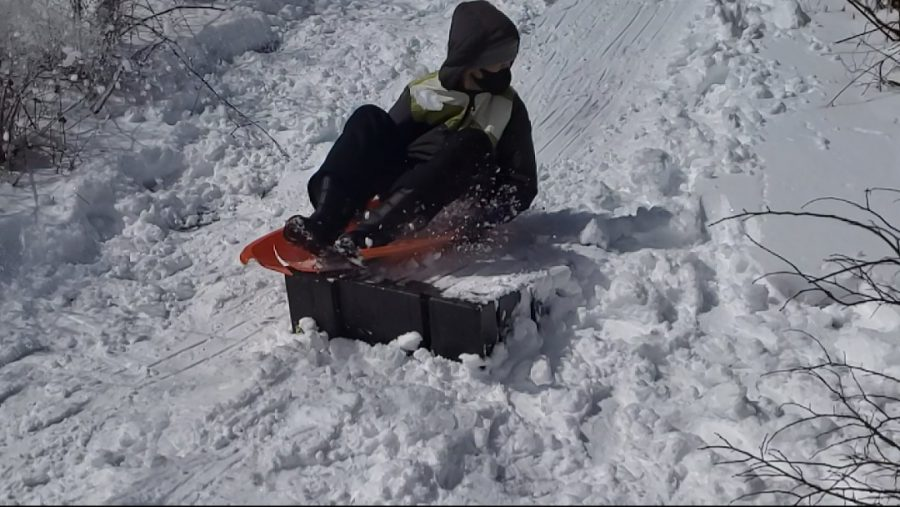 APPROACHING THE JUMP: Nicholas Wood prepares to launch off the ramp while sledding down the frozen slope in the nearby water reservoir. He's determined to achieve maximum airtime for an epic slow mo shot before the plastic sled becomes too damaged to be usable.